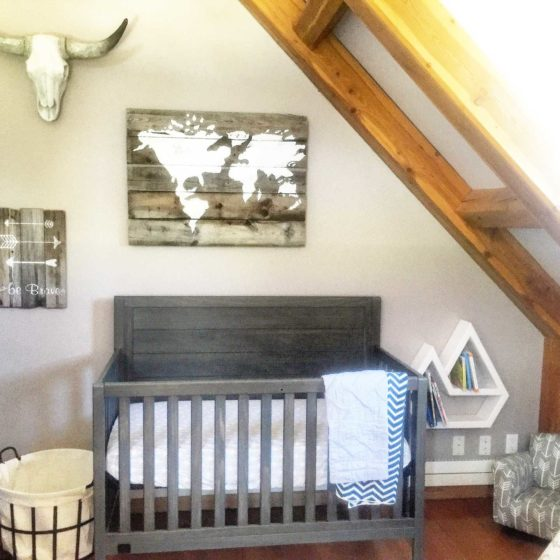 Vintage style decorated baby room with crib and wall art